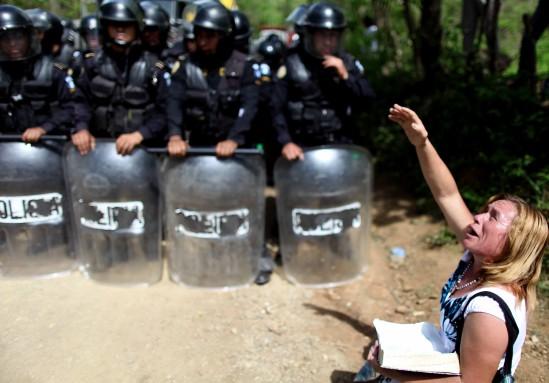Una mujer reza frente a los policías.