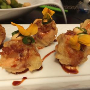 salmón y queso crema en tempura, aderezada con una salsa asiática y decorada con flores comestibles.