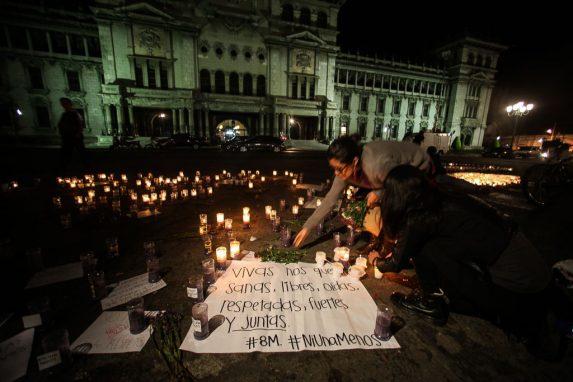 Mujeres prenden velas en la plaza central de la Ciudad de Guatemala.