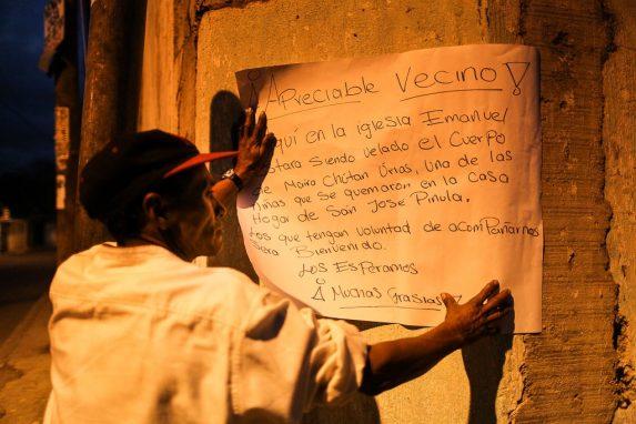 Un familiar cuelga un cartel afuera del velorio de Mayra.