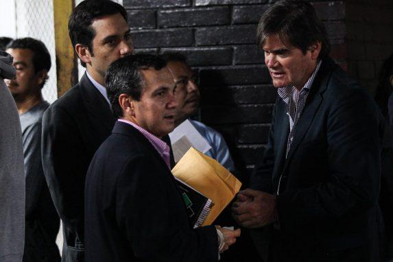 Mayorga (con un fólder) y Agüero (esposado) conversan al salir de tribunales ayer.
