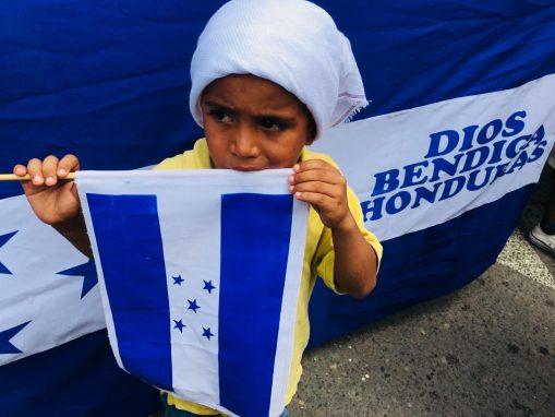 Un niño sostiene la bandera de Honduras. Después de atravesar Guatemala, la caravana intentó llegar a México por el puente internacional Rodolfo Robles.