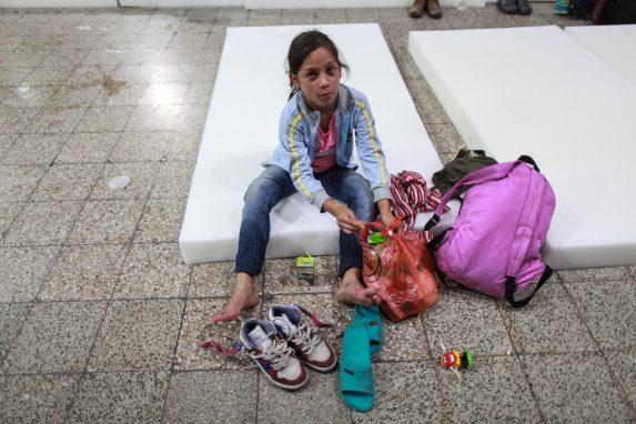 Una niña, unos tenis viejos, unas sandalias de plástico, un jugo en caja y un triste juguete en el piso de granito. La menor hondureña toma un descanso luego de un largo camino entre Chiquimula y la Ciudad de Guatemala.