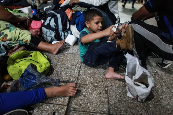 Lo primero, descansar. El camino es largo, cansado y peligroso para los niños que acompañan a sus papás. Cuando una parada segura los protege, se descalzan para aliviar el dolor en sus pies.