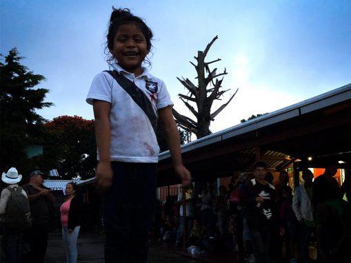 Una niña sonríe, aún porta una camisa de escuela. Sonríe porque ve apoyo de la gente que observa cómo una marea de hondureños se desplaza para escapar de la pobreza y la inseguridad con la esperanza de hallar en Estados Unidos una oportunidad para una vida más digna. (Foto: Pia Flores)