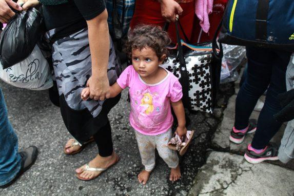 Un niña sostiene sus zapatos mientras descansa sus pies en el frío del asfalto. Tomada de la mano de su mamá, ve con incertidumbre el movimiento de personas y las decisiones que toman. Ella forma parte de los niños que acompañan la caravana de hondureños.