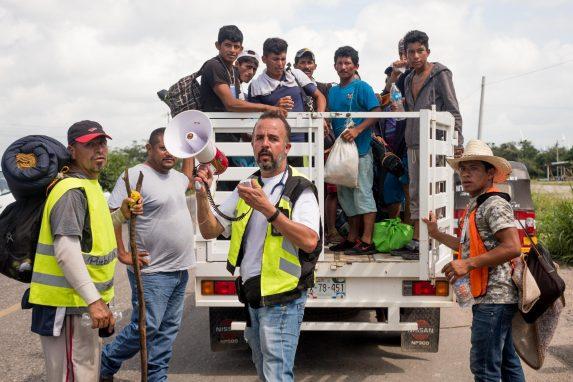 El doctor Manuel Valenzuela (centro con chaleco verde) es ejerce en el Paso, Texas, pero ahora acompaña la caravana como voluntario. En la foto, se encarga de conseguir aventones para los migrantes hacia la ciudad de Matías Romero, Oaxaca. 1 de noviembre de 2018. Foto: Fred Ramos
