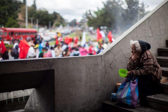 Una mujer pide dinero en una pasarela del Centro Cívico. Al fondo, la marcha que protesta contra Jimmy Morales.