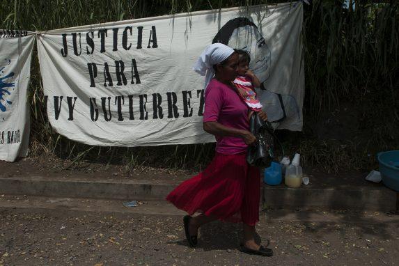 Una mujer y su hija pasan delante de un cartel en julio de 2018, en Sonsonate, en contra de las detenciones ilegales. El caso de Ivy Gutierrez fue el de una joven acusada en falso de extorsión por la policía en 2016 y absuelta por el juez en 2018.