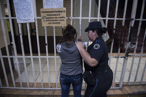 Una oficial del Sistema Penitenciario revisa a una mujer que cumple prisión preventiva por el delito de extorsión, mientras espera en el sótano de la Torre de Tribunales a su audiencia.