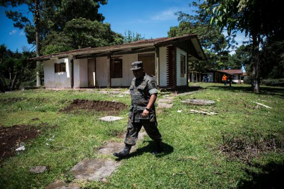 """En un recorrido para estudiar el proyecto habitacional ante la prensa, un miembro del ejército supervisa alrededor de la finca que perteneció al narcotraficante Marvin Montiel Marín alias """"El Taquero""""."""