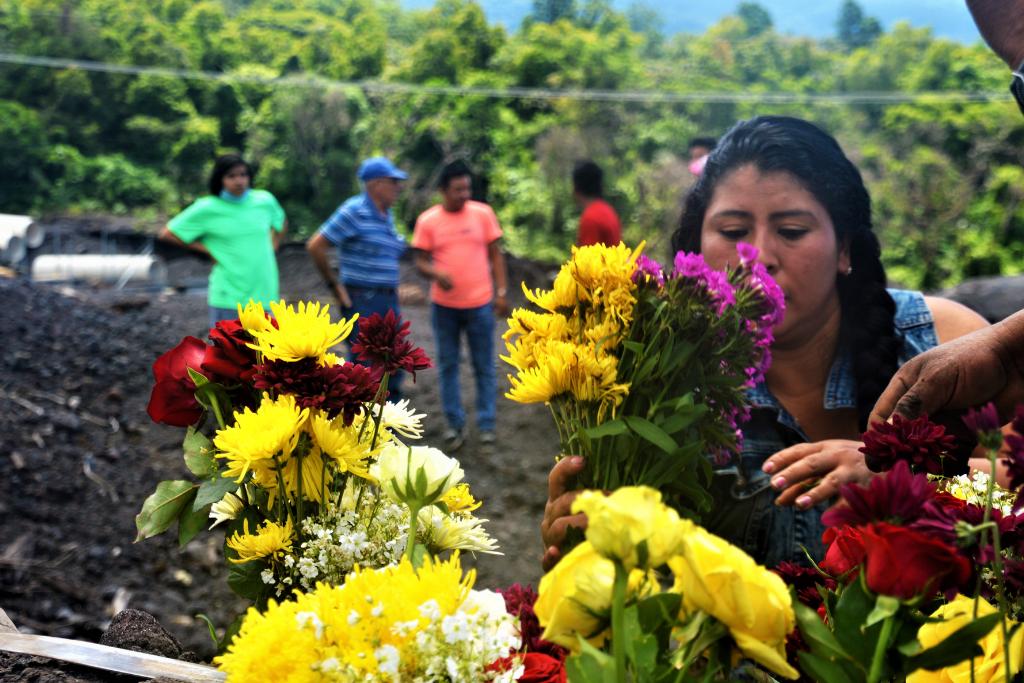 Una mujer deja flores en una de las casas sepultadas en San Miguel Los Lotes, donde fallecieron 13 de sus familiares. Foto: Asier Vera