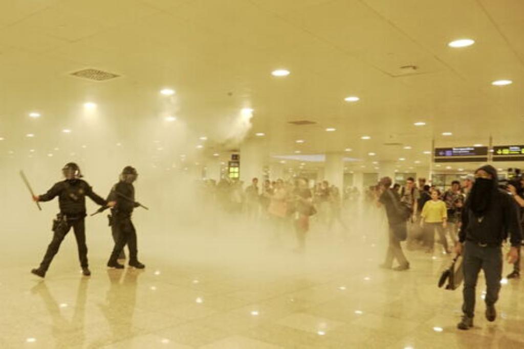 Dos policías en la terminal en medio de una nube de humo.