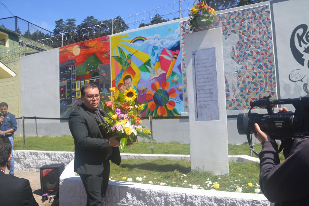 El subsecretario Marwin Bautista coloca una ofrenda floral en el monumento que el gobierno instaló en el Hogar Seguro Virgen de la Asunción.