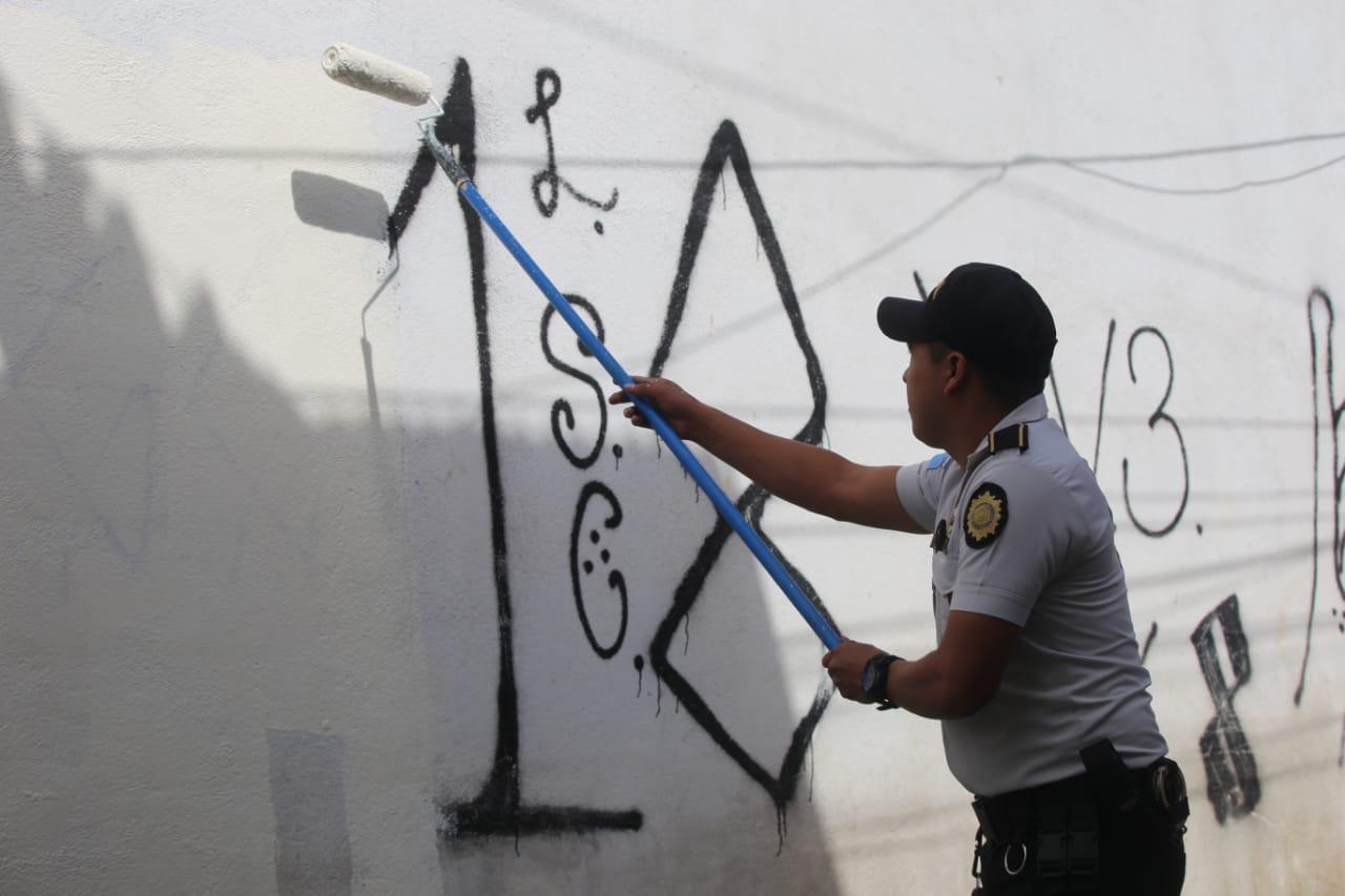 Policías borran graffittis de las pandillas en Mixco.
