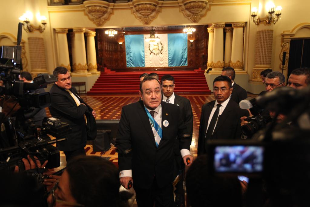 Giammattei atiende a los medios de comunicación, mientras Castillo observa desde atrás.