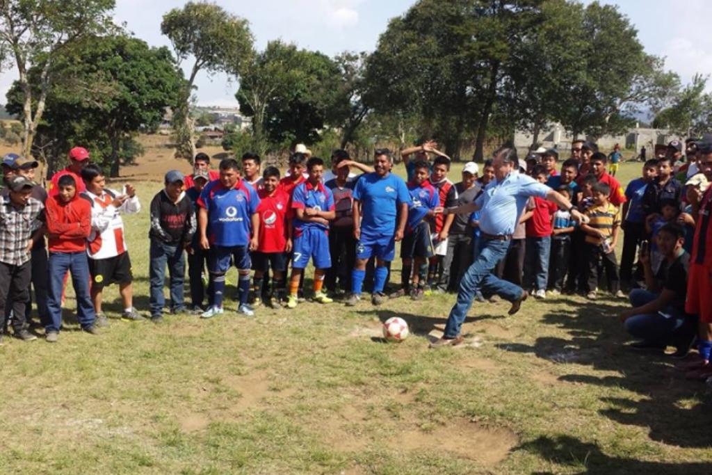 Mario Estrada patea un balón junto a jóvenes que lo observan. Era común verlo compartir con las comunidades. Su imagen era importante para cada campaña política.